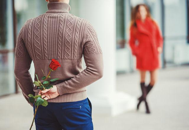 バラを後ろで持つ男性