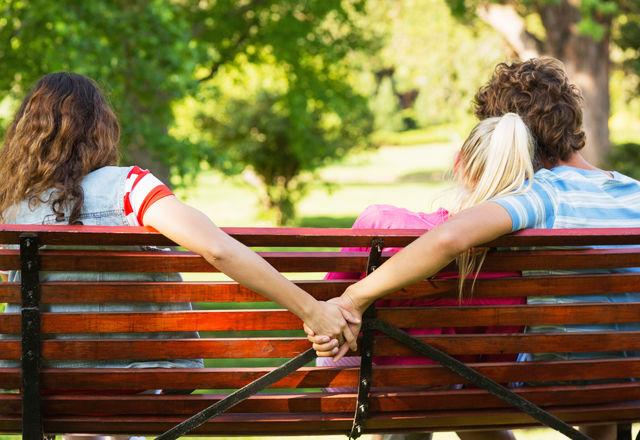 二人の女性と座る男性