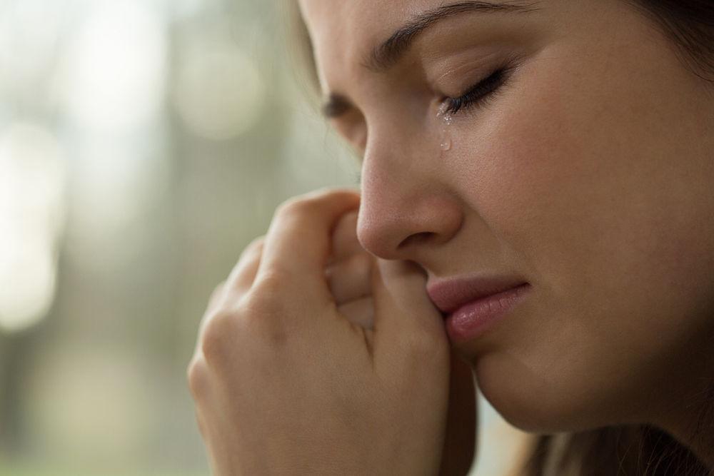 涙こらえる女性